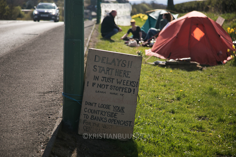 A small camp of two tents occupy the curb by the mining site 4 May 2018, County Durham. Sunset in Pont Valley ahead of the the day of protest against the mining company Banks outside Dipton in Pont Valley, County Durham, 4 May 2018. Locals have fought the open cast coal mine for thirty years and three times the local council rejected planning permissions but central government has overruled that decision and the company Banks was granted the license and rights to extract coal in early 2018. Locals have teamed up with climate campaigners and together they try to prevent the mining from going ahead. The mining will have huge implications on the local environment and further coal extraction runs agains the Paris climate agreement. A rare species of crested newt live on the land planned for mining and protectors are trying to stop the mine to save the newt.