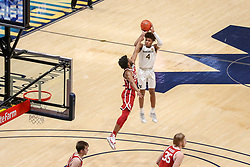 Feb 13, 2021; Morgantown, West Virginia, USA; West Virginia Mountaineers guard Miles McBride (4) misses a game winning jumper over Oklahoma Sooners guard Elijah Harkless (24) at the end of regulation at WVU Coliseum. Mandatory Credit: Ben Queen-USA TODAY Sports