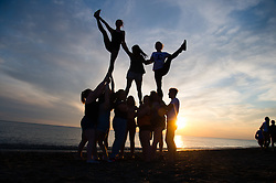 © Licensed to London News Pictures. 08/05/2016. Aberystwyth, Wales, UK. Girls from the Aberystwyth University American Football 'Tarannau' cheerleaders squad practice their stunts and exercises as the sun sets on Cardigan Bay in Aberystwyth on the West Wales coast .  Photo credit: Keith Morris/LNP