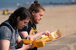 Portobello, Scotland, UK. 25 April 2020. Views of people outdoors on Saturday afternoon on the beach and promenade at Portobello, Edinburgh. Good weather has brought more people outdoors walking and cycling. The beach appears busy with possibly a breakdown in social distancing happening later in the afternoon. People eating chips on the promenade, a takeaway food stall is open.  Iain Masterton/Alamy Live News