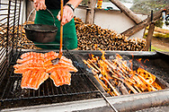 A man marinating salmon on a wood fired grill in Alaska.