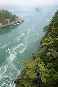 Tidal currents swirl through the strait in Deception Pass State Park, Whidbey Island, Washington, USA. State Route 20 crosses a scenic bridge 180 feet above Deception Pass, a strait of water separating Whidbey Island from Fidalgo Island. Deception Pass connects Skagit Bay (part of Puget Sound) with the Strait of Juan de Fuca, which are all part of the Salish Sea. Deception Pass is the most-visited State Park in Washington.