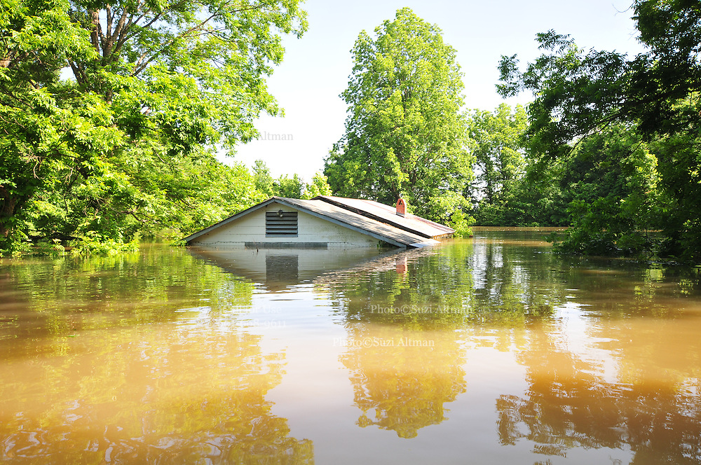 """8/13/11} Vicksburg} -- Vicksburg, MS, U.S.A<br />  --Robert Shiers aka Peanut paddles past his hand built cabin in the woods too check on the flood waters Friday May 13,2011 Peanuts flooded cabin on Chickasaw Road was a cabin in the woods is now a cabin on the flooded Mississippi River.  Hope and faith float as the Mississippi River continues to rise around the Kings Community on Friday the 13th of May 2011. """"Peanut """" aka Robert Shiers navigates his """"John Boat"""" down Chickasaw Rd. in Vicksburg Mississippi. His hand built ,self designed cabin which sits on 14ft. stilts on the old Belle Meade Plantation was on a 5acre wheat field that is now inundated with water and only able to get to by boat.  No mail today for residents of the Kings Community in Vicksburg MS Friday May 13, 2011.The Mississippi River in Vicksburg, Mississippi is expected to crest at a record 58.5 feet. The water is moving at 2.2million cubic feet per second, to put it in perspective it would fill the SuperDome in New Orleans in 30 seconds. Pictured is the historic Yazoo Valley Railroad Station in downtown Vicksburg. The River is flooding over 1.2 million acres of farm land and damaging thousands of homes and disrupting thousands of peoples lives. Vicksburg a riverfront town steeped in war and sacrifice, gets set to battle an age-old companion: the Mississippi River. The city that fell to Ulysses S. Grant and the Union Army after a painful siege in 1863 is marshaling a modern flood-control arsenal to keep the swollen Mississippi from overwhelming its defenses. PHOTO©SUZI ALTMAN.COM<br /> Photo by Suzi Altman"""