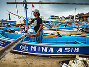 18 JULY 2016 - KUTA, BALI, INDONESIA:  A man gets his small outrigger canoe ready to go out to sea to go fishing at Pasar Ikan pantai Kedonganan, a fishing pier and market in Kuta, Bali.   PHOTO BY JACK KURTZ