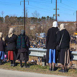 Gordonville, PA, USA - March 10, 2012: Amish women standing near a guard rail at the mud sale.
