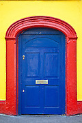 Brightly coloured red blue doorway yellow wall of Furlong's Bar in Passage East, Co. Waterford, Ireland