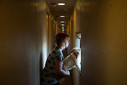 """Associate Production Manager Emily Ritter takes a moment to enjoy the sights on the train with her dog  Addie, who she picked up during one of their stops in Texas. Here, they enjoy the train ride between Richmond, VA and Washington DC.<br /> <br /> Ringling Bros. and Barnum & Bailey Circus started in 1919 when the circus created by James Anthony Bailey and P. T. Barnum merged with the Ringling Brothers Circus. Currently, the circus maintains two circus train-based shows, the Blue Tour and the Red Tour, as well as the truck-based Gold Tour. Each train is a mile long with roughly 60 cars: 40 passenger cars and 20 freight. Each train presents a different """"edition"""" of the show, using a numbering scheme that dates back to circus origins in 1871 — the first year of P.T. Barnum's show."""