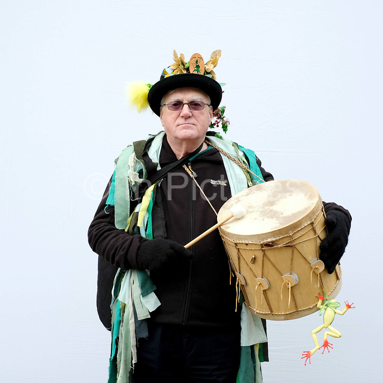 Portrait of a Makara Morris musician wearing traditional costume at an orchard-visiting wassail at Sledmere House in the Yorkshire Wolds, United Kingdom on 20th January 2018. Wassail is a traditional Pagan winter celebration in cider-producing regions of England, reciting incantations and singing to the trees to promote a good harvest for the coming year. Pieces of toast soaked in cider are hung in the branches to attract robins to the tree as these are said to be the good spirits of the orchard. To ward off evil spirits, villagers scare them away by banging pots and pans and making as much noise as possible