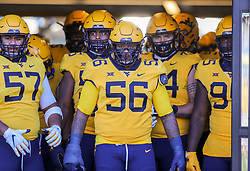 Oct 31, 2020; Morgantown, West Virginia, USA; West Virginia Mountaineers defensive lineman Darius Stills (56) leads his team onto the field before their game against the Kansas State Wildcats at Mountaineer Field at Milan Puskar Stadium. Mandatory Credit: Ben Queen-USA TODAY Sports