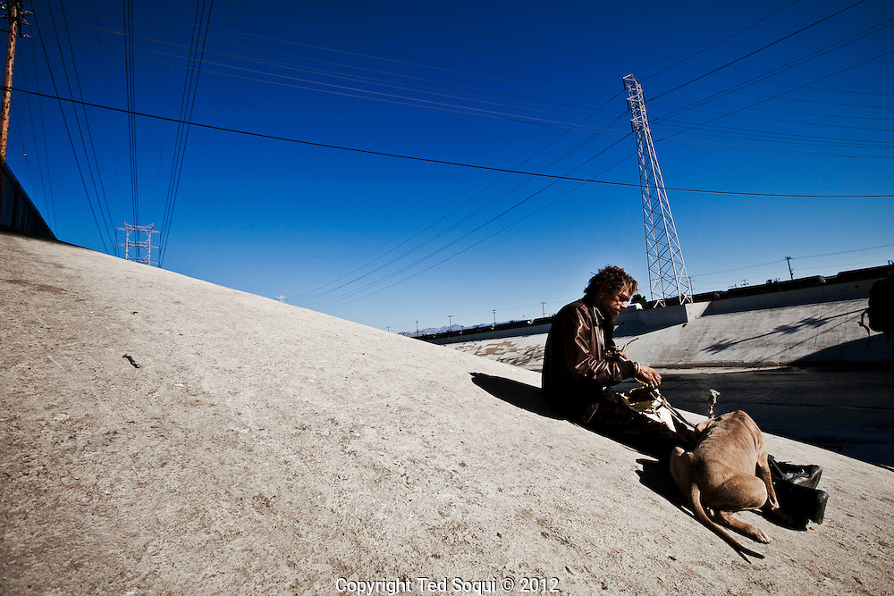 A homeless man and his dog rest on the banks of the LA River.