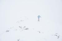Hiker in winter conditions hiking through deep snow towards summit of Schneibstein (2276 m),  Hagengebirge, Berchtesgaden Alps, Germany - Austria