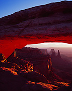 Mesa Arch sunrise with view through arch to Washer Woman Arch, Monster Tower, Airport Tower and the La Sal Mountains, Island in the Sky, Canyonlands National Park, Utah.