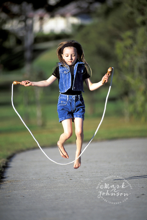 Australia, Qld., little girl jumping rope people ****Model Release available