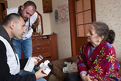 Doctor Khachatur Malakyan (l) and nurse Andrei Bogma (2nd l) during an MSF home visit in Debaltsevo. Lina and her mother, Lydia, (r) live in a small apartment with Lina's two young daughters and her husband. They try to care for their grandmother who suffers from Parkinson's disease.