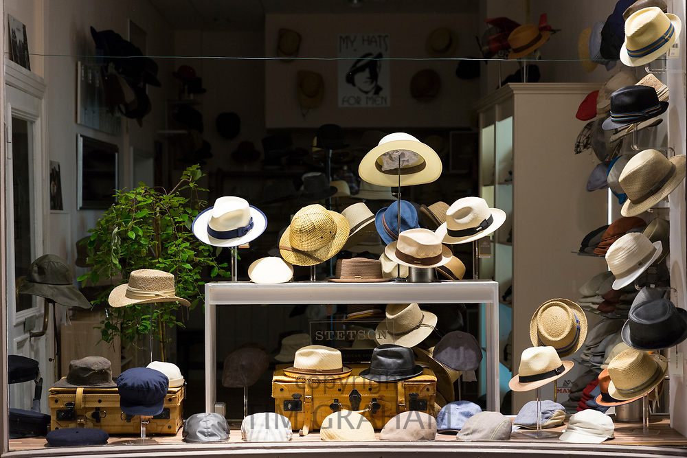 Display of men's hats - panama hats, berets, caps in clothing shop window, Lubeck, Northern Germany
