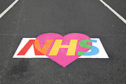 Colourful NHS love heart logo in support of NHS staff and key workers painted onto the street at Westminster as lockdown continues and people observe the stay at home message in the capital on 11th May 2020 in London, England, United Kingdom. Coronavirus or Covid-19 is a new respiratory illness that has not previously been seen in humans. While much or Europe has been placed into lockdown, the UK government has now announced a slight relaxation of the stringent rules as part of their long term strategy, and in particular social distancing.