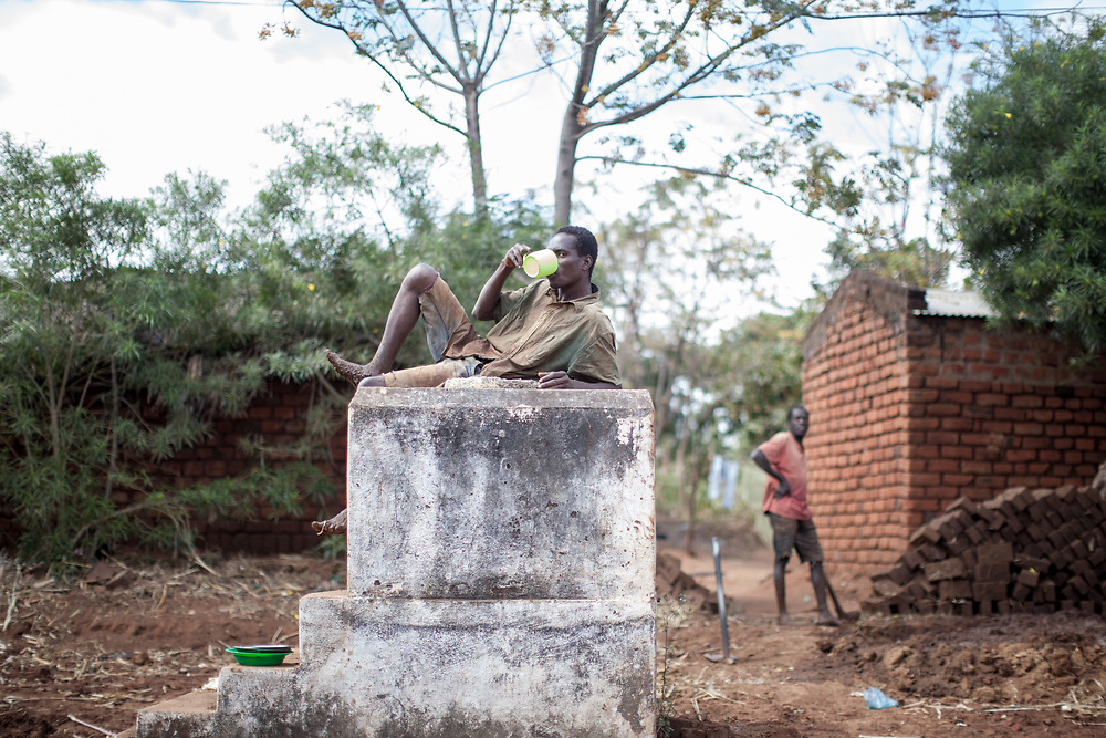 A man reclines and drinks from a cup atop a water tank in southern Malawi