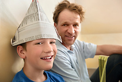 Boy paper hat father smiling bonding fun