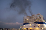 Diesel smoke pours from the funnels of Brittany Ferries roll-on / roll-off car and vehicles ferry as the engines start up prior to departure on 14th September 2021 in Plymouth, United Kingdom. Brittany Ferries is the trading name of the French shipping company, BAI Bretagne Angleterre Irlande S.A. founded in 1973 by Alexis Gourvennec, that operates a fleet of ferries and cruise ferries between France and the United Kingdom.