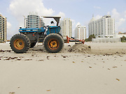 Tractor cleaning the beach with hotels in the background Miami Beach USA