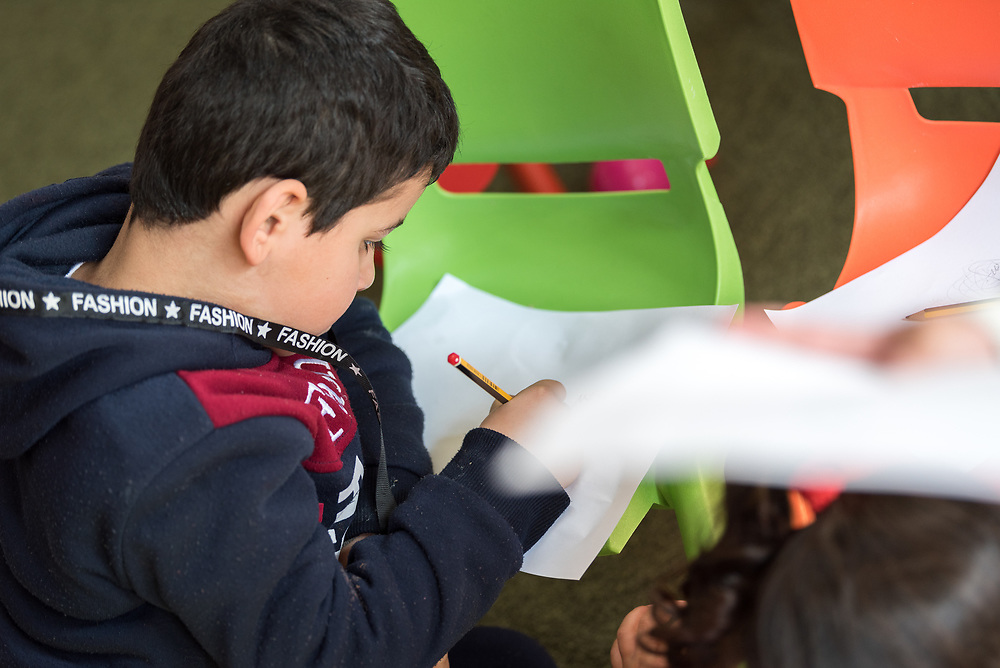 17 February 2020, Zarqa, Jordan: A boy sits down to write in the 'nanny room' of the Lutheran World Federation community centre in Zarqa. Through a variety of activities, the Lutheran World Federation community centre in Zarqa serves to offer psychosocial support and strengthen social cohesion between Syrian, Iraqi and other refugees in Jordan and their host communities.
