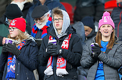 Crystal Palace fans keep warm in the stands ahead of the Premier League match at the John Smith's Stadium, Huddersfield.