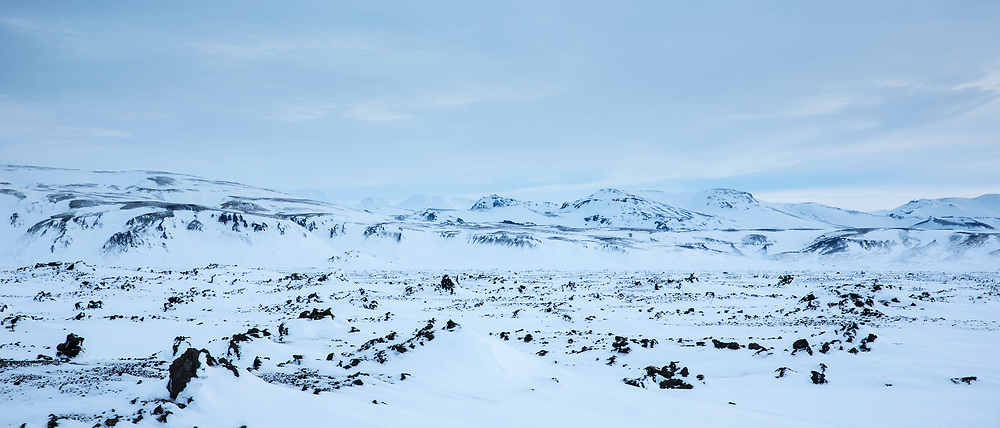 Empty landscape of mountains and snow-covered lava fields of volcanic rock by Sultartangastoo in the highlands of South Iceland