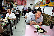 Man eating Chinese dumplings for breakfast in a small restaurant in Xuanwu district, an area just south of Tiananmen in Beijing, China.