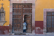 A Mexican man looka out at street life from a colonial style wooden door along Juarez Street in San Miguel de Allende, Mexico.