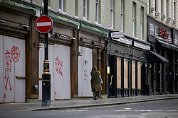 © Licensed to London News Pictures. 25/11/2020. London, UK. A woman walks past boarded cafés and bars in Soho, central London, which are currently closed as part of a national lockdown to slow the spread of the Coronavirus. The government has announced that tiered restrictions will be reintroduced when the England-wide lockdown ends on 2 December. Photo credit: Rob Pinney/LNP