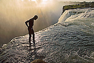 A man takes a moment of reflection at the top of Victoria Falls.