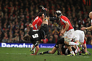 James Hook of Wales tackles Sam Whitelock of the Allblacks (5). Invesco Perpetual match, Wales v New Zealand at the Millennium stadium in Cardiff on Sat 27th Nov 2010.  pic by Andrew Orchard, Andrew Orchard sports photography,