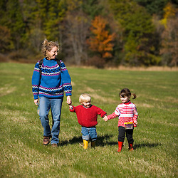 A woman and her young children explore a field on the Common Pasture in Newburyport, MA.