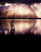 Sun rays streaming through rain shower falling over Twin Lakes and the Volcanic Mountains, Lake Clark National Park, Alaska.