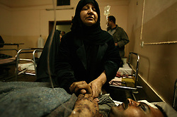 Baija Khader comforts her son Falah Hassan, 35, a would-be recruit for the Iraqi Army, at Al Karah hospital, Baghdad, Iraq, Feb. 11, 2004. A suicide attacker detonated a car packed with explosives in a crowd of hundreds of Iraqis waiting outside a Baghdad army recruiting center Wednesday, killing up to 46 people in the second bombing in two days targeting Iraqis working with the U.S.-led coalition. The attack backed threats that insurgents would step up violence to disrupt the planned June 30 handover of power to the Iraqis.