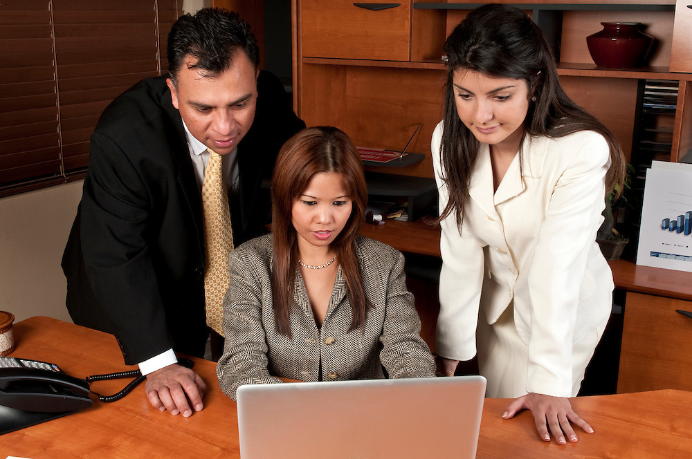 Group of coworkers working together in small business looking at computer.