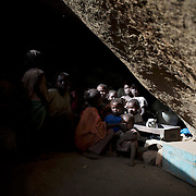 April 28, 2012 - Buram, Nuba Mountains, South Kordofan, Sudan: A Nuba family takes cover, from possible bombardments by Sudan's Army Forces airplane, in some caves near Buram village. Since the 6th of June 2011, the Sudan's Army Forces (SAF) initiated, under direct orders from President Bashir, an attack campaign against civil areas throughout the South Kordofan's province. Hundreds have been killed and many more injured...Local residents, of Nuba origin, have since lived in fear and the majority moved from their homes to caves in the nearby mountains. Others chose to find refuge in South Sudan, driven by the lack of food cause by the agriculture production halt due to the constant bombardments of rural areas.