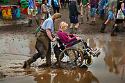 Wheelchars trying to negocite the chaos caused by heavy rain which created a mud bath in the Glastonbury Festival 2016, United Kingdom. Glastonbury Festival is the largest greenfield festival in the world, and is now attended by around 175,000 people. Its a five-day music festival that takes place near Pilton, Somerset. In addition to contemporary music, the festival hosts dance, comedy, theatre, circus, cabaret, and other arts. Held at Worthy Farm in Pilton, leading pop and rock artists have headlined, alongside thousands of others appearing on smaller stages and performance areas.