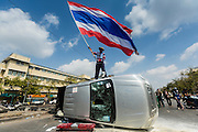 18 FEBRUARY 2014 - BANGKOK, THAILAND: An antigovernment protestor waves a Thai flag from atop a police vehicle protestors overturned in Bangkok. Anti-government protestors aligned with Suthep Thaugsuban and the People's Democratic Reform Committee (PDRC) clashed with police Tuesday. Protestors opened fire on police with at rifles and handguns. Police returned fire with live ammunition and rubber bullets. The Bangkok Metropolitan Administration's Erawan Emergency Medical Centre reported that three civilians and a policeman were killed and 64 others were injured in the clashes between police and protesters.    PHOTO BY JACK KURTZ