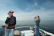 assistant scientist Monica Zani listens for whale calls with a hydrophone while research intern Johanna Anderson uses binoculars to scan the ocean for North Atlantic right whales aboard the New England Aquarium research vessel Nereid, Grand Manan Basin, Bay of Fundy ( North Atlantic Ocean )