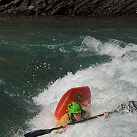 Kayaker Mikkel St. Jean-Duncan plays in waves on the Kananaskis River in the Canadian Rockies near Calgary, Alberta.