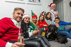 Left - right Lee Simms, 40, his partner Miriam, 39, Lee's former partner Barby Ford, 35, daughters Sofia, 9, Florencia 12, Charlie, 11 and Barby's husband Mike Ford, 37 crowd onto the sofa with Alonso their two year-old spaniel cross.. Brighton, December 16 2018.