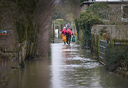 © Licensed to London News Pictures. 04/02/2021. Little Marlow, UK. Residents carry shopping as they make their way through floodwater near Little Marlow in Buckinghamshire after the river Thames burst its banks. Large parts of the UK have experienced more wet conditions bringing further flooding . Photo credit: Peter Macdiarmid/LNP