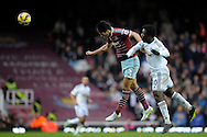 James Tomkins of West Ham United heading the ball over Wilfried Bony of Swansea City. Barclays Premier league match, West Ham Utd v Swansea city at the Boleyn ground, Upton Park in London on Sunday 7th December 2014.<br /> pic by John Patrick Fletcher, Andrew Orchard sports photography.