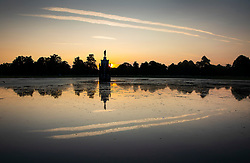 © Licensed to London News Pictures. 24/06/2020. London, UK. Aircraft contrails line the sky as the sun rises behind the Diana Fountain in Bushy Park, south west London. High temperatures and sunshine are expected in most of the UK over the next few days. Photo credit: Peter Macdiarmid/LNP