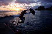 "Silhouette of man carrying ""boogie board"" jumping into water to body surf. Waikiki, Honolulu, Hawaii"