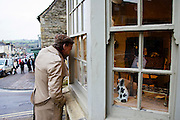 Man peers through an Antiques shop window in Burford in the Cotswolds, United Kingdom