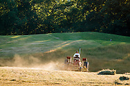 Mount Hope, New York - A farmer drives a tractor though a hay field at Pierson Farm on June 16, 2016.