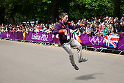 London, UK. Tuesday 7th August 2012. Men's Triathlon held in Hyde Park. A volunteer brings the crowd to life before the competitors come through.