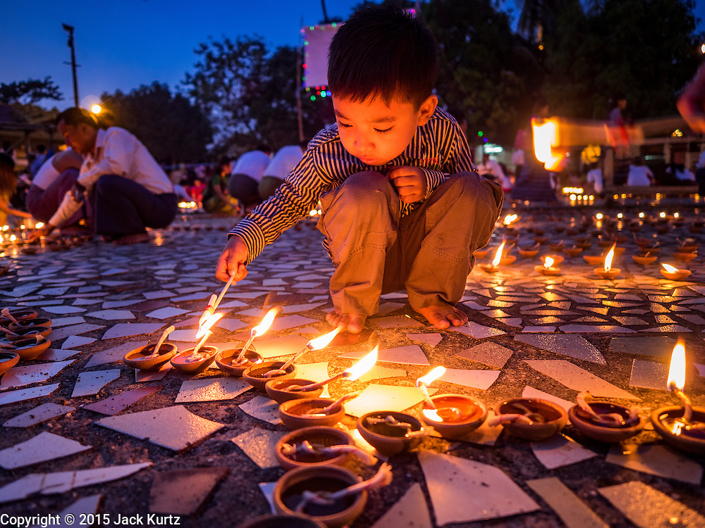 28 OCTOBER 2015 - YANGON, MYANMAR: A boy lights oil lamps during observances of Thadingyut at Botataung Pagoda in Yangon. Botataung Pagoda was first built by the Mon, a Burmese ethnic minority, around the same time as was Shwedagon Pagoda, over 2500 years ago. The Thadingyut Festival, the Lighting Festival of Myanmar, is held on the full moon day of the Burmese Lunar month of Thadingyut. As a custom, it is held at the end of the Buddhist lent (Vassa). The Thadingyut festival is the celebration to welcome the Buddha's descent from heaven.    PHOTO BY JACK KURTZ
